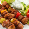 kebab-skewers-vegetables-sauce-cucumber-tomato-lettuce